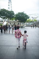 Bike lesson (jeremyhughes) Tags: singapore marinabay bicycle bike child cycling bikelesson grandparent granny gran outdoor lesson teaching cyclist childhood riteofpassage nikon d700 nikkor 50mm 50mmf14d street city leisure pink