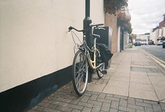 black and yellow bike (johnnytakespictures) Tags: disposable disposablecamera singleuse smile pocketsocket 35mm film analogue leamingtonspa leamington warwickshire bike bicycle cycle wheels transport vintage retro classic street chain chained lock locked black yellow