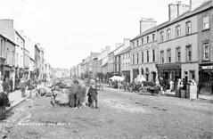 Main Street, Longford on a market day (National Library of Ireland on The Commons) Tags: robertfrench williamlawrence lawrencecollection lawrencephotographicstudio thelawrencephotographcollection glassnegative nationallibraryofireland mainstreet longford countylongford ireland marketday carts produce animals children dog johnboyers draperoutfitter shops merchandise bowler farrell