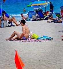 Caution on the beach (LarryJay99 ) Tags: 2018 beach streets people ftlauderdale ocean atlanticocean orange flag shirtless speedo back shoulders glasses sandy tanning man men guy guys dude male studly manly dudes handsome seated sunglasses hotdudes saggers shirtlessguys legs hairy hairylegs tattoos tatts