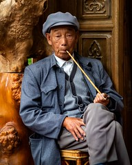 A Quiet Pipe (Rod Waddington) Tags: china chinese yunnan shaxi pipe smoking man streetphotography portrait candid people culture cultural sitting cap wood outdoor
