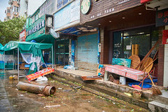 After Typhoon Mangkhut 04 (C & R Driver-Burgess) Tags: typhoon hurricane wind damage devastation destruction road street vehicle broken fallen smashed tree branch leaves trunck bicycle motorcycle scooter shopfront pavement sidewalk construction site fence building