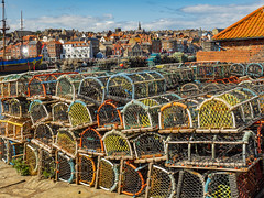 Pots of many Colours (Ian M Bentley) Tags: whitby yorkshire seaside seasidetown coast lobsterpots pots stackedcolours northridingofyorkshire beautyspot streanæshealh path olympus omd em1ii 1240mmprolens wideangle f28lens summer august england uk outdoor landscape red yellow green blue sky lobsters crayfish trap birds town