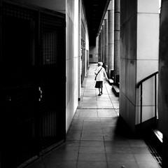 Looking for her path (pascalcolin1) Tags: paris paris12 femme woman chemin way passage path couloir corridor lumiere light colonnes columns ombres shadows photoderue streetview urbanarte noiretblanc blackandwhite photopascalcolin 50mm canon50mm canon