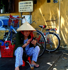 Just give me a minute while I take this call (bushman58929) Tags: streettraders vietnam hoian travel tourist bushman58929 olympus digital captured colors