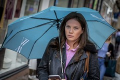 Blue Eyes (Leanne Boulton) Tags: portrait urban street candid portraiture streetphotography candidstreetphotography candidportrait streetportrait eyecontact candideyecontact streetlife blueeyes young woman female girl face eyes expression mood feeling emotion wet weather rain raining umbrella blue pink colourful brunette tone texture detail depthoffield bokeh naturallight outdoor light shade city scene human life living humanity society culture lifestyle people canon canon5dmkiii 70mm ef2470mmf28liiusm color colour dutchangle glasgow scotland uk
