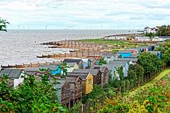 Behind the Beach Huts (Geoff Henson) Tags: beachhuts beach huts foliage tree breakwater sea water ocean clouds building windmill windfarm ship dog