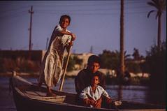 Sailing on the swamp of Nassaryah. (rvjak) Tags: f3 nikon marais swamp irak iraq kids enfants jeunes young boat bateau barque middleeast moyenorient film argentique pellicule water eau rame trois three