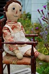 Raggedy Ann in the Garden (Emily1957) Tags: volandraggedyannoldchairgarden antique antiquedoll light naturallight nikon nikond40 shoebuttoneyes doll dolls toy toys handmade ragdoll johnnygruelle paintedface woodenheart vollandraggedyann
