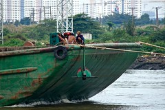 Day's Work Done:  Incoming Sand Delivery, Port Saigon (Ginger H Robinson) Tags: daysworkdone boat barge sand transport portsaigon saigonriver vietnam southeastasia river water shore building city anchor asia
