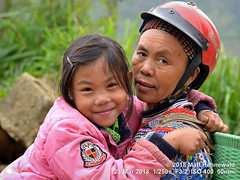 2018-03d Northeast Vietnam (63) (Matt Hahnewald) Tags: matthahnewaldphotography facingtheworld people head face eyes expression lookingcamera smile highspirits soulfulness story crashhelmet bodylanguage bothhands hugging closeembrace consent emotion relationship concept humanity living travel culture lifestyle love enjoyment happiness joy upbringing childhood affection ethnic tribal minority rural village grandmother grandchild sincheng laocai northern vietnam asian vietnamese hmong twopeople female child elderly woman photo nikond3100 primelens nikkorafs50mmf18g 50mm 4x3 horizontal street portrait doubleportrait halflength closeup outdoor color posing cute authentic smiling joyous depthoffield clarity nose running