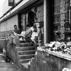 Never closed (Go-tea 郭天) Tags: huangdao qingdao shandong boss husband wife family 2 together love business lazy shop duty wait waiting mess messy relax relaxing relaxed couple opened boxes sunglasses newspaper phone cellular cell cellphone network connected connexion data read reading news stairs up upstairs street urban city outside outdoor people candid bw bnw black white blackwhite blackandwhite monochrome naturallight natural light asia asian china chinese canon eos 100d 24mm prime man woman lady