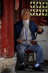 Blind Erhu Player  (in explore) (Rod Waddington) Tags: china chinese violin twostringed instrument erhu musical playing player building yunnan seat indoor performance window column wooden pavilion