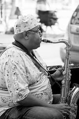 Street Musician (DJ Wolfman) Tags: saxaphone streetshots streetphotography streetphoto streetscene blackandwhite bw man instrument sunshine hat olympusomd olympus em1markii micro43 panasonic panasonic35100f28