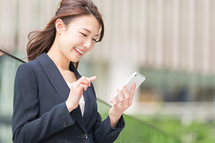619997100 (creative guide) Tags: smartphone whitecollarworker buildingexterior businesswoman women females smiling holding japaneseethnicity asianethnicity business technology urbanscene outdoors officeworker occupation people japan day springtime suit