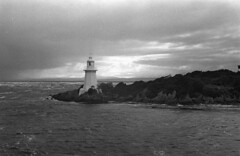 The Devils Lighthouse (Harald Philipp) Tags: outdoors rural seascape isolated natural scenic ocean sea bay water waterfront shore holiday vacation tourism tourist exotic destination travel adventure wanderlust island ilford delta400 film grain analog filmphotography 35mm retina sky australia tasmania strahan penalcolony dark rain badweather highseas stormfront lighthouse storm blackandwhite bw
