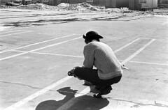 020571 34 (ndpa / s. lundeen, archivist) Tags: nick dewolf nickdewolf blackwhite blackandwhite 35mm film bw february 1971 1970s boston massachusetts cambridge lechmere lechmeresales firststreet parkinglot photographbynickdewolf man nd car modelcar rccar rc radiocontrolled hat vw volkswagen bug beetle snow meltingsnow