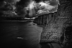 "The sun punching through storm clouds over Falaise d'Amont (Cliffs of Amont) moody, brooding, fine art black & white view. Étretat, Seine-Maritime, Haute-Normandie, Normandy, France (grumpybaldprof) Tags: bw blackwhite ""blackwhite"" ""blackandwhite"" noireetblanc monochrome ""fineart"" ethereal striking artistic interpretation impressionist stylistic style contrast shadow bright dark black white illuminated étretat seinemaritime hautenormandie normandy france arches ""portedaval"" ""portedamont"" ""portedemanneporte"" laiguille ""theneedle"" ""eugèneboudin"" ""gustavecourbet"" ""claudemonet"" ""paysdecaux"" ""alabastercoast"" ""chapellenotredamedelagarde"" ""thewhitebird"" ""loiseaublanc"" ""lachapellenotredamedelagarde"" ""falaised'amont"" ""thegardensofetretat"" ""lesjardinsd'etretat"" alabaster cliffs needles sun rays storm mood moody atmosphere atmospheric dramatic sea rock canon 70d ""canon70d"" tamron 16300 16300mm ""tamron16300mmf3563diiivcpzdb016"""