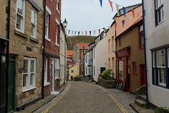 High Street, Staithes (Walruscharmer) Tags: cobbledstreet doubleyellowlines buildings dwellings holidaycottages captainjamescook bunting clevelandway nationaltrail e2europeanlongdistancepath northseatrail englandcoastpath nationalpark northyorkmoors northyorkshire yorkshire england