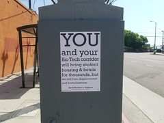 Anti-USC Biotech and anti-gentrification posters in Lincoln Heights on the utility box at Griffin and Main.