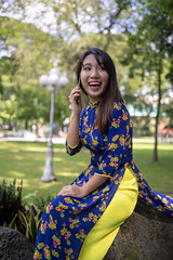 Young woman in Ao Dai talking over the phone in public park (Apricot Cafe) Tags: img105572 aodai asia asianandindianethnicities hochiminhcity millennialgeneration tamronsp35mmf18divcusdmodelf012 vietnam vietnameseethnicity break carefree colorimage day greencolor happiness lifestyles longhair mouthopen nature oneperson oneyoungwomanonly outdoors people photography portrait publicpark realpeople refreshing serenepeople sitting smartphone smiling straighthair sunlight talking threequarterlength tourism tourist traditionalclothing travel women youngadult