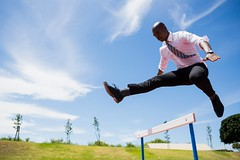 Businessman jumping a hurdle while running (nithiyabhaskar) Tags: running jumping career hurdle while 2529 well racing track sophisticated concentration determination conceptual20s difficulties entrepreneur professional athleticism businessman competition performance opportunity profession milestones corporate challenge ethnicity business obstacle olympics athletic overcome olympic dressed efforts focused african leaping athlete stylish elegant vision future classy years sunny young sport smart black ireland