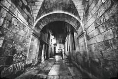 Along the Dark Alley (henriksundholm.com) Tags: backstreet street night tunnel shadows stone rock flagstones wideangle urban city bw blackandwhite monochrome alicante spain espana