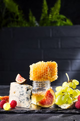 Grape, cheese, figs and honey on a stone black background over brick black wall with green flower, copy space (lyule4ik) Tags: cheese wine grape board food french red glass delicatessen gourmet appetizer snack background white italian wood fruit bottle alcohol dairy wooden plate france table brie camembert drink product various wineglass walnut dinner party yellow beverage goat holiday meal parmesan restaurant sweet assorted honey nut cuisine bordeaux vine autumn tasty art