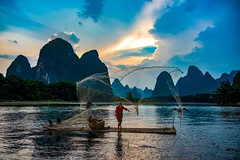 Cormorant Fisherman on the Li River (Rod Waddington) Tags: china yangshuo li river lijiang net fishing fisherman bamboo raft water mountains karst sunset clouds evening throwing cormorants nature landscape