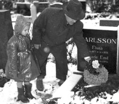 Visiting a grave (theirhistory) Tags: child kid girl father grave stone snow coat hat raincoat waterproof wreath wellies boots shoes