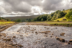SJ1_0795 - An exuberant River Swale near Muker (SWJuk) Tags: swjuk uk unitedkingdom gb britain england yorkshire northyorkshire yorkshiredales dales swaledale river riverswale muker water shallows light sunlight shadows landscape countryside scenery trees fields hills hillside sky skies clouds greysky 2018 sep2018 autumn holidays nikon d7200 nikond7200 18300mm rawnef lightroomclassiccc