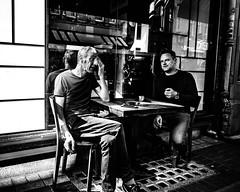 Stealth check (Kieron Ellis) Tags: man men coffee sitting smoking phone keys table chairs window reflection wall pavement street candid blackandwhite blackwhite monochrome