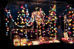 The Night Vendor of Spheres with Light Centers (Matt Molloy) Tags: mattmolloy photography night vendor person booth colourful hanging lights spheres strings circles glow red orange yellow green blue purple pink white pikachu chiangmai thailand lovelife