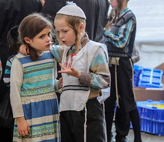 Intimacy -- Sharing (ybiberman) Tags: israel jerusalem meahshearim yomkippur dayofatonement feast kapparotmarket boy girl people ultraorthodox jews portrait candid streetphotography payot tzitzit tallit yarmulke kippah braids dress