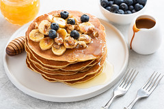 Stack of pancakes with banana, blueberries, walnuts, honey and caramel sauce (Arx0nt.) Tags: pancake stack american blueberry breakfast dessert food gourmet homemade honey caramelsauce lunch pastry plate sweet tasty traditional banana fresh healthy maplesyrup bakery closeup delicious fruit heap meal nutrition snack walnut shrovetuesday golden nobody cooked selectivefocus caramel gluten top brunch background pile appetizing whitebackground russian cuisine roast cream wooden corn sauce