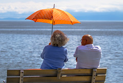 The Umbrella (Paul Rioux) Tags: people humans couple seascape seashore waterfront ocean sea water sun sunny day sitting bench umbrella shade mountains orange prioux