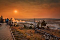 Sunset on the Boardwalk (KPortin) Tags: fence boardwalk yellowstonenationalpark sunset sun geyser steam people
