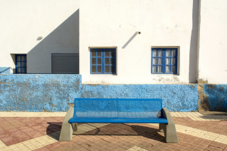 Blue bench, wall and windows.