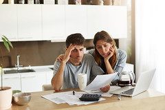Unhappy American Couple Managing Home Accounts In Kitchen, Trying To Save Some Money By Cutting Fami (ceneje.jeftinije) Tags: accounting apartment bank bankruptcy bill budget calculate calculator caucasian computer counting couple debt depression documents family female finance financial home house husband indoors kitchen laptop loan male man money paper paperwork paying payment people person problem receipt relationship serious stress stressed tax technology together two unhappy wife woman worried young
