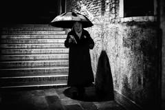 Canareggio (markfly1) Tags: woman waling wet umbrella steps stairway wall texture moisture long coat costume jewellery shadow light shade bright black white mono monochromatic candid street image nikon d750