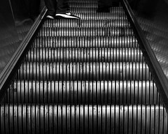 Going Up (Red Line Series No. 28) (briburt) Tags: briburt olympus lumix micro43 microfourthirds omdem5mkii 25mm alewife station thet redline escalator shoes simple up bw monochrome blackandwhite transit subway masstransit trainstation eerie ghost ghostly dramatic filmsimulation motion blur energy contrast silver metallic metal boston cambridge newengland movement transportation architecture urban city bigcity street streetphotography em5 lumix25mmf17 lines geometric massachusetts abstract somewhatabstract