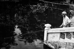 It's always safer to fish with a helmet (rvjak) Tags: hanoï vietnam d750 nikon southeast asia asie sudest pêcheur fisherman water eau lake lac noir blanc black white bw monochrome helmet casque cane stick reflet reflection contrast homme man