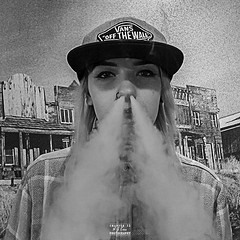 aje_2008_8015 (A J Evans) Tags: vaping girlvaping bw balckandwhite portraite grainy grainybackground nosering baseballcap wildwestbackground checkedshirt blonde blondehair shadedeyes
