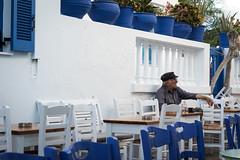 Coffee & Cigarettes (Adrià Páez) Tags: coffee cigarettes man sitting chairs tables bar cafe smoking greek greece ellada koufonisia pano cyclades europe blue white plants 50mm chora canon eos 7d mark ii street