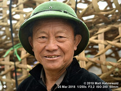 2018-03d Northeast Vietnam (77) (Matt Hahnewald) Tags: matthahnewaldphotography facingtheworld people character head face eyes wrinkles expression smile story shaved hat helmet pithhelmet north vietnamese army green consent concept humanity living dedication commitment culture tradition ethnic tribal minority hilltribe rural traditional cultural market village lungphinh laocai northern vietnam asia asian hmong individual oneperson male man adult physiognomy nikond3100 primelens nikkorafs50mmf18g 50mm horizontal street portrait closeup headshot fullfaceview outdoor posing powerful authentic smiling manly strong clarity 4x3ratio 1200x900pixels resized middleaged lookingatcamera colour