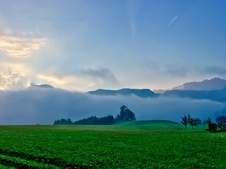 Fields, mountains and low clouds at sunrise near lake Hechtsee in Tyrol, Austria