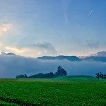 Fields, mountains and low clouds at sunrise near lake Hechtsee in Tyrol, Austria thumbnail