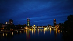 Frankfurt Serenade (Nathalie_Désirée) Tags: mariodraghi ezb ecb europeancentralbank europäischezentralbank mainhattan frankfurt main frankfurtonmain frankfurtammain bluehour evening serenade river water waterscape reflection house houses building buildings architecture skyscrapers skyscraper high skyline canoneos600d sigma1020mm tower bridge coophimmelblau bank banking finance financial shore strand waterside promenade night city urban ignatzbubisbrücke floesserbrücke flöserbrücke arches arch ignatzbubisbridge