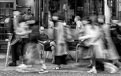 The world rushes by (David Feuerhelm) Tags: momochrome bw blackandwhite noiretblanc schwarzundweiss blancoynegro contrast blur slowshutterspeed people street cambridge england nikon d750 70200mmf28 movement streets