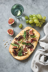 Flatbread pizza with prosciutto, figs, arugula (Arx0nt.) Tags: pizza flatbread gourmet arugula background cheese figsandprosciutto baked bread wine topview grape concrete cuisine delicious dinner fig parmesan food fresh homemade prosciuttoham italian meal prosciutto rustic snack tasty vegetable free gluten top paper meat above detail glass table drink spice red autumn alcohol wooden caramelizedonion sweet balsamicsauce fall piece eating
